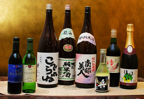Various alcoholic drinks including local sakes are prepared for dinner.